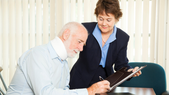 An elderly man wearing a light blue long sleeve polo and beside her is a woman assisting him to sign a document