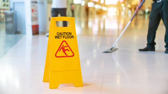 A white shining tiled floor with caution wet floor stand
