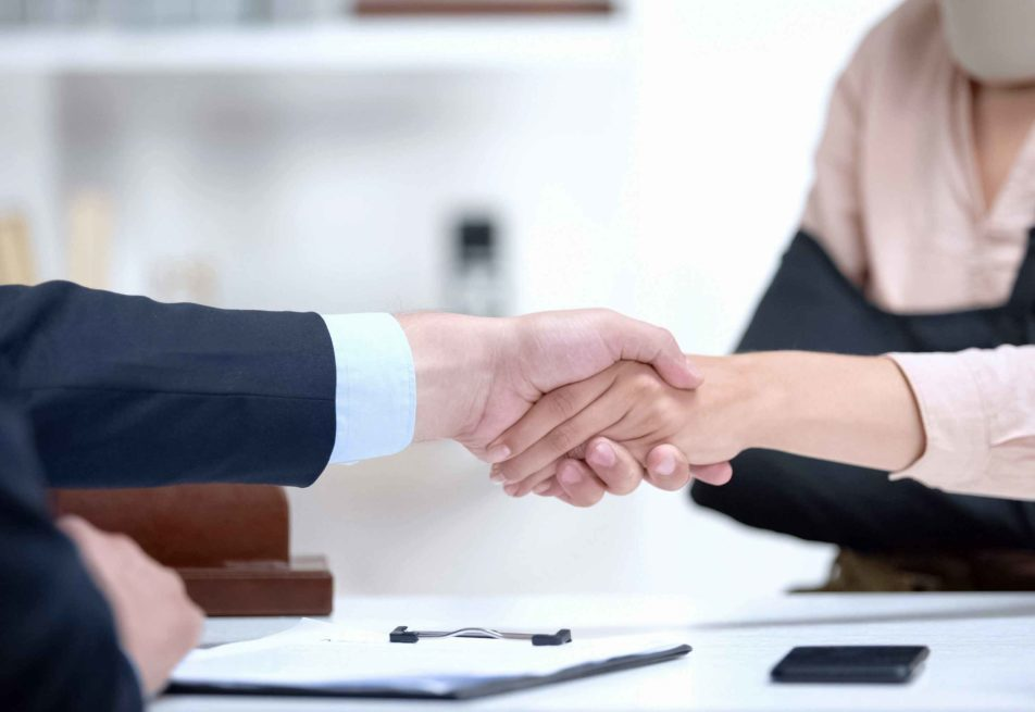 Two business people are shaking hands with papers in the table