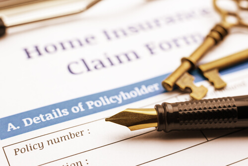 A pen and key place above the insurance claim form